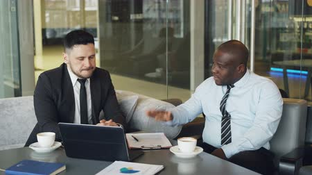criticize : Angry businessman in shirt an tie criticizes severely his partner during meeting in modern cafe. Irritated african american boss gesticulates emotionally and agressively talking Stock Footage