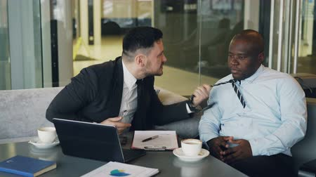 criticize : Angry bussinessman in suit scolding his african american employee and grabs his tie pointing on fail in contract at modern cafe. Angry boss striking table with his hand nervously Stock Footage