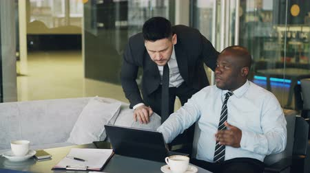 yapıcı : Confident african ceo gives guidelines to bearded caucasian manager in business suit standing nearby in modern cafe. African American businessman sits pointing at his laptop computer
