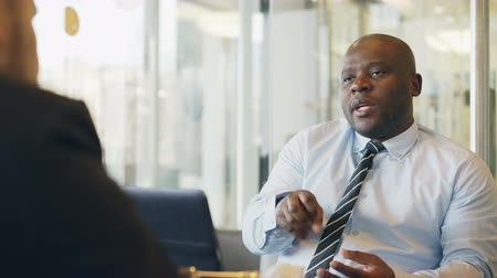 casual wear businessman : African American businessman gesticulating and explaining his startup details to investor in formal wear in glassy cafe during lunch time Stock Footage
