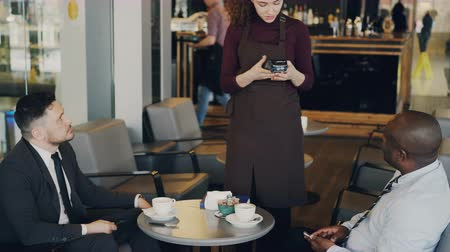 garçonete : Two multiracial businessmen in formal wear pay online bill using smartphone in modern cafe. Young waitress standing and keeping portable cash terminal.