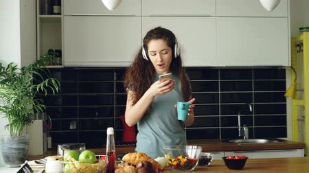 morning : Attractive happy girl dancing and singing in kitchen while using smartphone and listening to music at home in the morning
