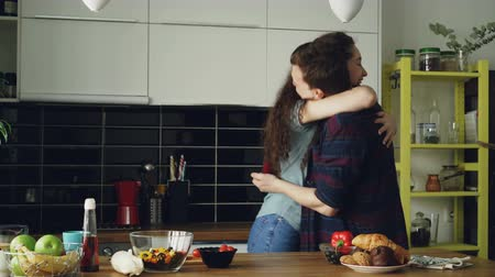 fiancee : Young man making proposal to his girlfriend while she cooking in the kitchen at home. He putting ring on her finger and kissing happy girl