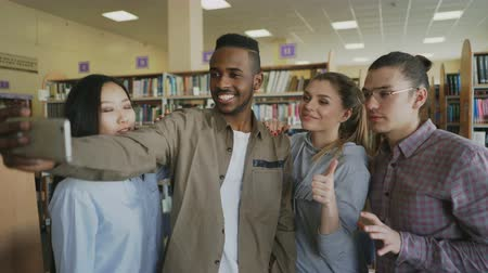 self examination : Group of international students have fun smiling and making selfie photos on smartphone camera at university library. Cheerful friends have rest while preapre project together