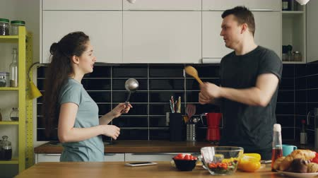 nowożeńcy : Happy couple having fun in the kitchen fencing with big spoons while cooking breakfast at home Wideo