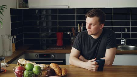 sonolento : Portrait of young caucasian man sitting at table in modern spacious kitchen, looking through window, drinking tea, he is tired and upset,closing eyes with hands Stock Footage