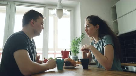 standing at table : young caucasian couple sitting at table in modern lighty spacious kitchen dicussing something in positive way, they are drinking tea, smiling, woman is beautiful Stock Footage
