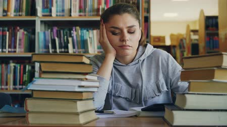 lesson : Beautiful caucasian teenage woman is sitting at table in university library holding digital tablet. She is tired and exhausted, shaking her head and writing in copybook Stock Footage