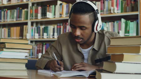 písanka : Handsome african american male student wearing headphones is listening to music sitting at table in big spacious library writing lecture surrounded by books Dostupné videozáznamy