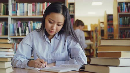 prateleira de livros : Young beautiful asian female student is sitting at table surrounded by piles of books in big library rewriting text from textbook getting ready for exam Stock Footage