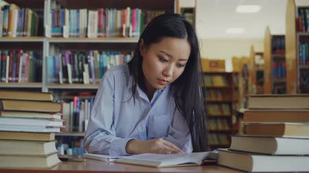 adormecido : Young asian teenage girl is sitting at desk in big library rewriting text from book. She is tired and exhausted, looking through text closing book and turning away Vídeos