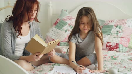 písanka : Young mother helps her little cute daughter with homework for elementary school. Loving mom reading a book and girl writing notes in copybook while sitting together on bed at home