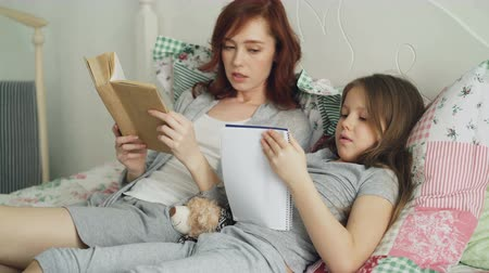 písanka : Careful mother helping her little cute daughter with homework for elementary school. Loving mom reading a book and girl writing notes in copybook while sitting together on bed at home