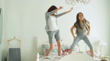 leaping : Funny little girl with her loving mother have fun dancing modern style together jumping on bed during morning at home