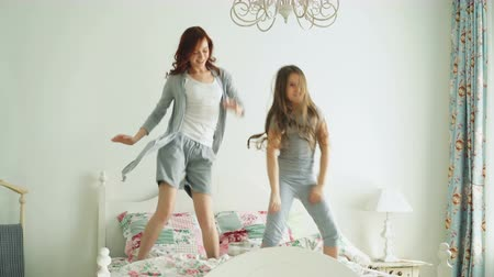 leaping : Funny little girl with her loving mother have fun learning dance modern style together watching dancing show on TV and jumping on bed during morning at home