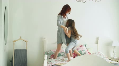 leaping : Happy family of cute daughter and young mother jumping and dancing on bed while have fun during morning on holidays at home Stock Footage