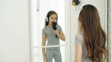 bochechudo : Beautiful little girl dancing and singing with hair comb in front the mirrorand have fun at home