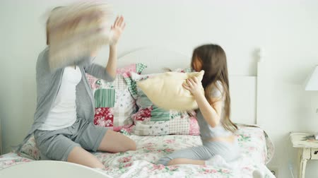buta : Happy cute daughter and young mother in pajamas fighting pillows sitting on bed while have fun in cozy light bedroom during holidays at home Stock mozgókép