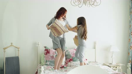 chmýří : Happy little daughter and young mother in pajamas fighting pillows on bed while have fun in cozy bedroom during vacation at home