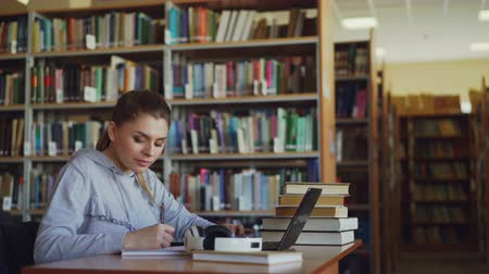домашнее задание : Young beautiful smiling student girl is sitting at desk in big spacious library with pile of books. She is writing something in copybook, laptop is in front of her