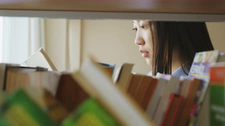 looking for : Attractive asian student girl standing near shelf with books in university library holding book turning over pages reading it Stock Footage