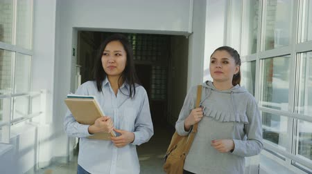 lobby : Two young beautiful female students walking in wide lighty corridor of college discussing homework smiling positively. Asian girl is holding books and papers.