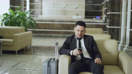 lobi : Pan shot of concentrated businessman using smartphone sitting on armchair inside luxury hotel with luggage near him