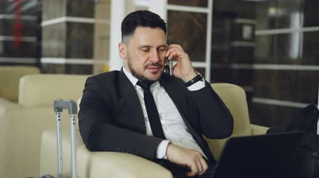 lobby : Tilt up of confident businessman talking mobile phone and using laptop computer while sits on armchair in luxury hotel with luggage near him. Travel, business and people concept