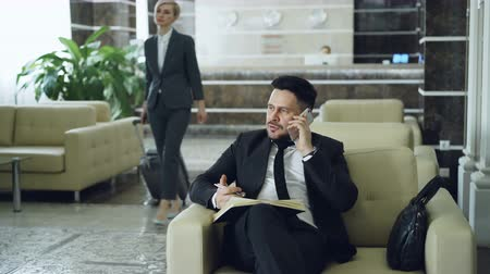 lobi : Pan shot of handsome bearded businessman sitting in armchair talking mobile phone with notepad while businesswoman with luggage walking through hotel lobby from reception desk