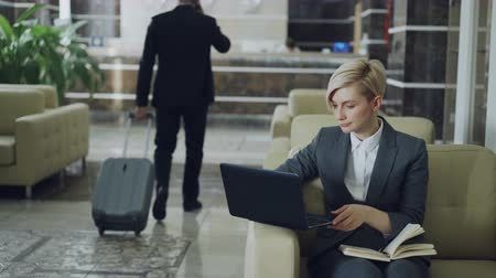karczma : Blonde businesswoman sitting in armchair with notepad and laptop computer while businessman with luggage walking through hotel lobby to reception desk Wideo