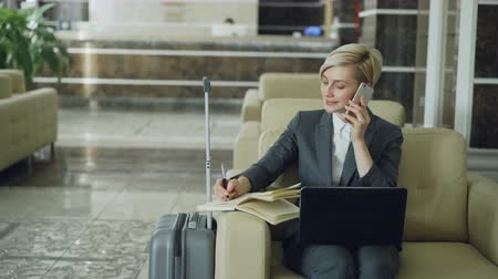 liga : Pan shot of blonde busy businesswoman sitting in armchair in hotel lobby talking mobile phone, writing in notepad and using laptop computer. Business, travel and people concept