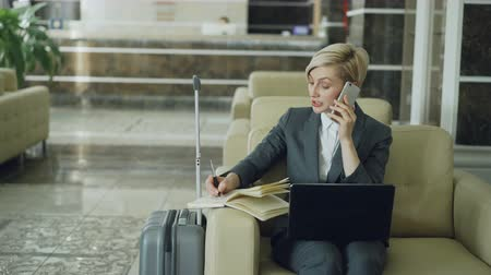 karczma : Pan shot of blonde busy businesswoman sitting in armchair in hotel lobby talking mobile phone, writing in notepad and using laptop computer. Business, travel and people concept