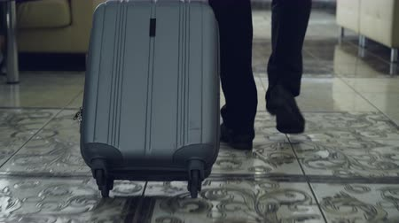 pulling up : Dolly shot of legs of businessman walking through hotel lobby pulling luggage and stop at reception desk. Business, travel and people concept