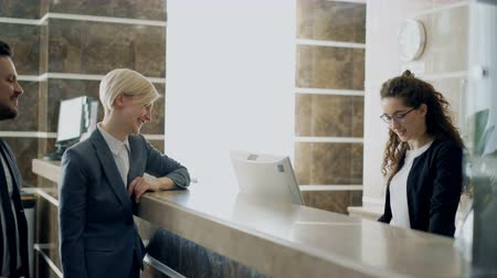 szállás : Receptionist girl talking with arrived businessman and businesswoman guests about check-in in hotel and giving key card from room to man . Business, travel and people concept Stock mozgókép