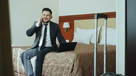 karczma : Tilt up of smiling businessman in suit working on laptop and talking at mobile phone while sitting on bed in hotel room. Business, travel and people concept