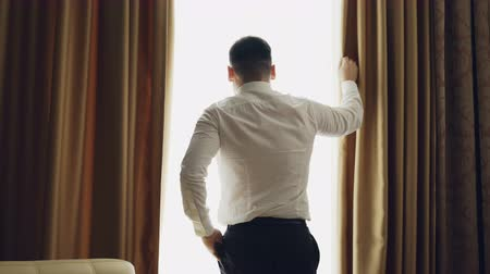 persons : Businessman unveil curtains in hotel room at the morning and looking into window