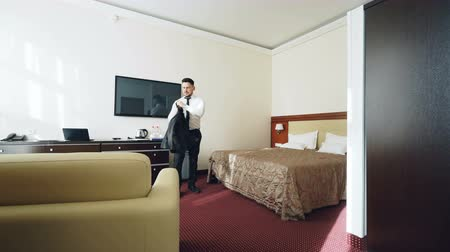 Войти : Businessman with luggage entering hotel room and jumping on bed happily then lying relaxed smiling. Travel, business and people concept Стоковые видеозаписи