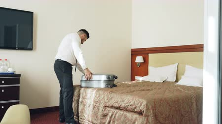 dobrável : Businessman packing his suitcase and leaving hotel room at check-out time. Travel, business and people concept