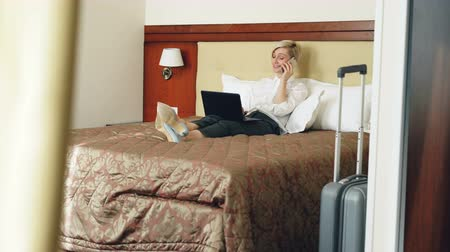 karczma : Smiling businesswoman in white shirt using on laptop and talking at mobile phone while lying on bed in hotel room. Business, travel and people concept Wideo