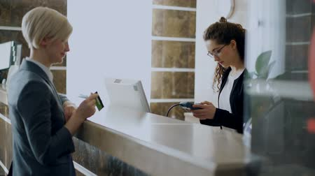 payment : Businesswoman guest in hotel reception paying bill contactless payment credit card technology and talking with receptionist girl standing at desk. Business, travel and people concept