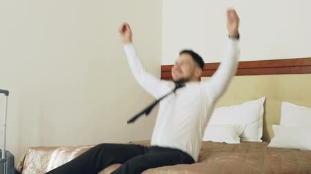 прибытие : Slow motion of Happy businessman jumping on bed at hotel room and lying relaxed smiling. Business, travel and people concept Стоковые видеозаписи