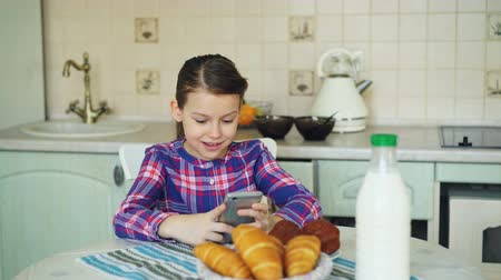 croissants : Little beautiful girl playing smartphone at morning while sitting at table in kitchen. Childhood, people, and technology concept