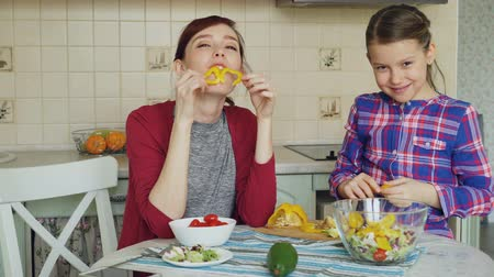 ostoba : Joyful mother and cheerful daughter have fun grimacing silly with vegetables and looking into camera while cooking in the kitchen at home. Family, cook, and people concept
