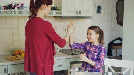 girl claps : Happy mother and cute funny daughter playing clapping hands game and have fun while cooking in kitchen at home. Family, cooking and people concept Stock Footage