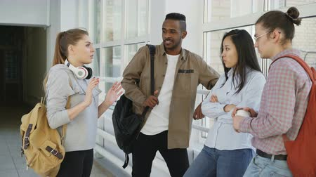 higher : Dolly shot view of multi-ethnic group of students standing together in corridor of college. Beautiful caucasian girl is standing on front of them explaining and gesturing Stock Footage