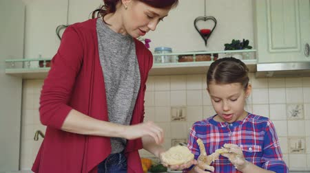 muffin : Happy mother and cute daughter cooking together and having fun stirring dough in hands in kitchen. Family, food, home and people concept Stock Footage