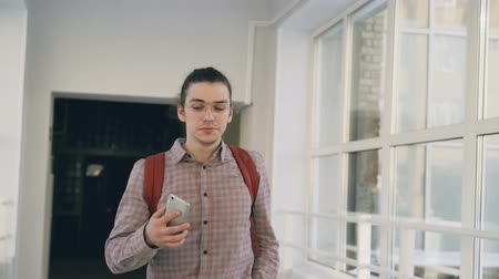 go to school : Young handsome caucasian hipster male student is walking in white lighty spacious corridor in college holding phone making phone call passing by other students