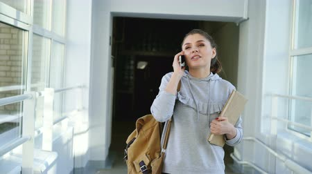 go to school : Dolly shot view of beautiful pretty female student walking down university corridor talking on phone holding textbook passing by foreign students near window Stock Footage