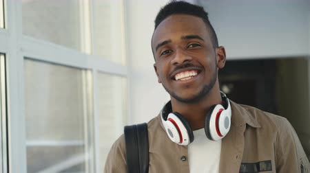 higher : Portrait of young handsome student of african-american ethnicity standing in wide white spacious corridor of college with hedphones looking at camera and smiling