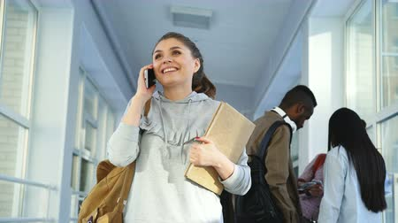 telefonkönyv : Portrait of young beautiful female student wearing casual clothes talking on phone in positive way while her groupmates are standing behind her discussing something Stock mozgókép